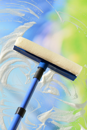 window glass: Cleaning windows with special squeegee