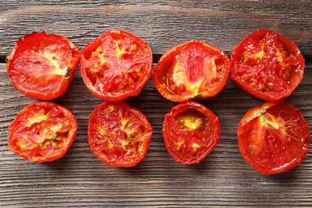 mini oven: Delicious baked tomatoes on wooden background Stock Photo