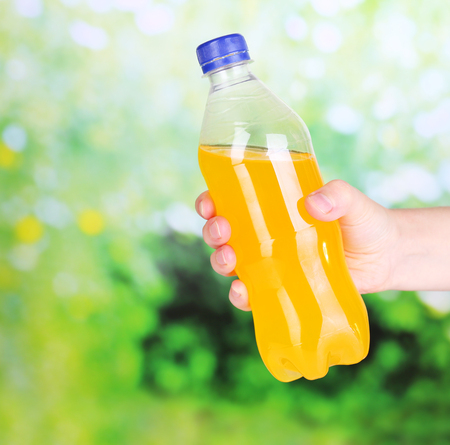 Hand opening bottle with sweet water on natural background