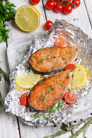Tasty baked fish in foil on table close-up photo