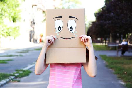 cara triste: Mujer con caja de cartón en la cabeza con la cara triste, al aire libre