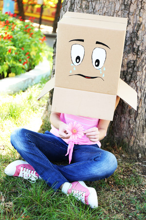 the art of divination: Woman with cardboard box on her head with sad face, holding flower, outdoors
