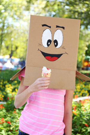 woman face cream: Woman with cardboard box on her head with happy face holding ice cream, outdoors