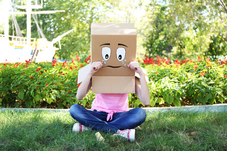 woman face cream: Woman with cardboard box on her head with sad face and ice cream on green grass, outdoors Stock Photo
