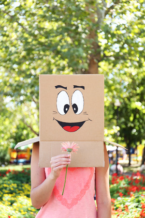 the art of divination: Woman with cardboard box on her head with happy face, holding flower, outdoors