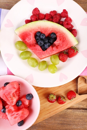filled out: Fresh juicy watermelon slice  with cut out heart shape, filled fresh berries, on plate, on wooden background