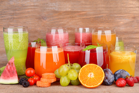 Glasses of tasty fresh juice, on wooden table. Stock Photo