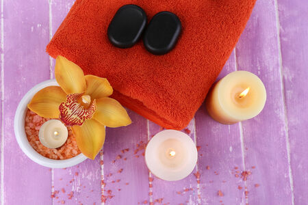 Still life with beautiful blooming orchid flower, towel and sea salt in bowl on color wooden background photo