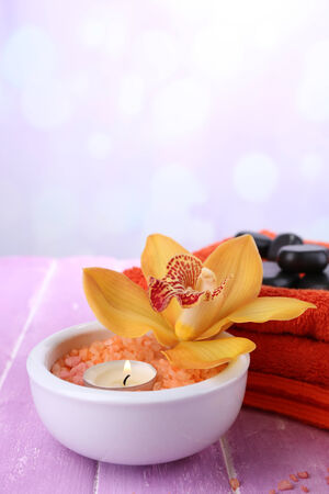 Still life with beautiful blooming orchid flower, towel and sea salt in bowl on color wooden table, on bright background photo
