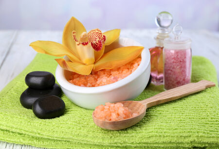 Still life with beautiful blooming orchid flower, towel and sea salt in bowl on color wooden table, on light background photo