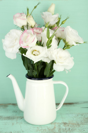 Beautiful eustoma flowers in teapot, on wooden background photo
