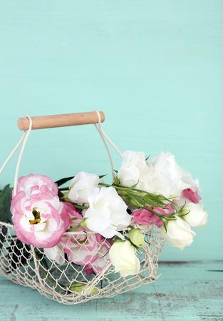 Beautiful eustoma flowers in basket, on wooden background photo