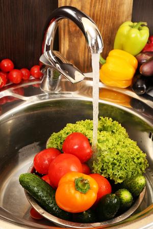 Fresh vegetables in sink in kitchen photo