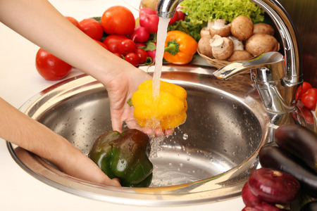 Womans hands washing pepper in sink photo