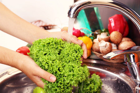 Womans hands washing vegetables in sink in kitchen photo