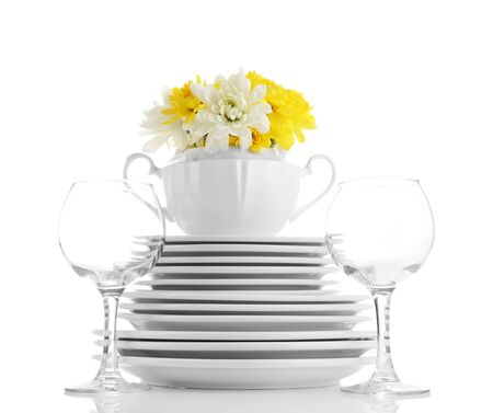Stack of white ceramic dishes and flowers, isolated on white photo