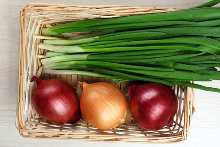close up of onions in a basket: Different raw onion on wooden