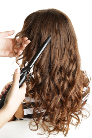 curling irons: Stylist using curling iron for hair curls, close-up, isolated on white