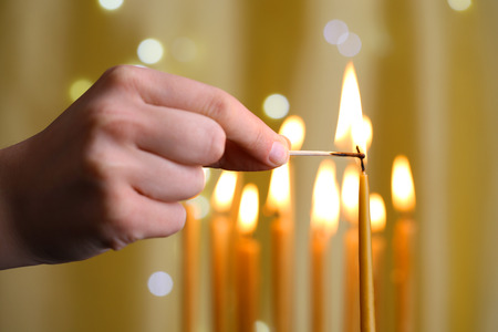 easter candle is burning: Hand lighting candle Stock Photo