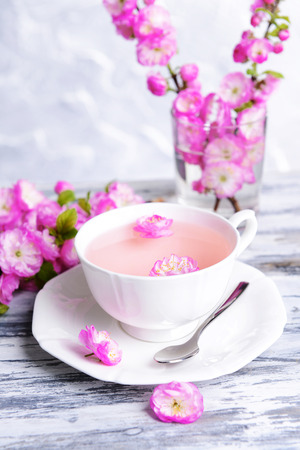Beautiful fruit blossom with cup of tea on table on grey background photo