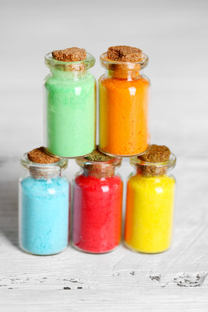 pigments: Bottles with colorful dry pigments on wooden background