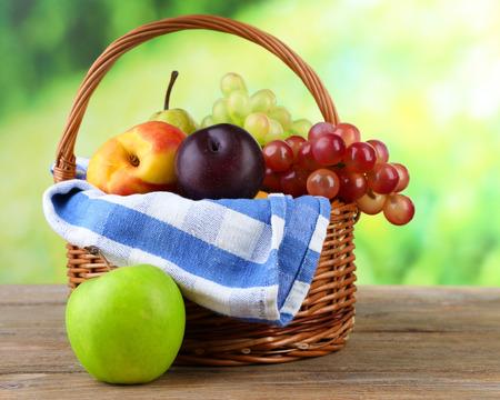 canasta de frutas: Surtido de frutas jugosas en cesta de mimbre en la mesa, en el fondo brillante Foto de archivo