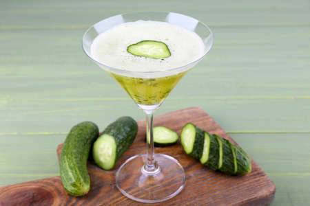 clarification: Cucumber cocktail on cutting board on wooden background