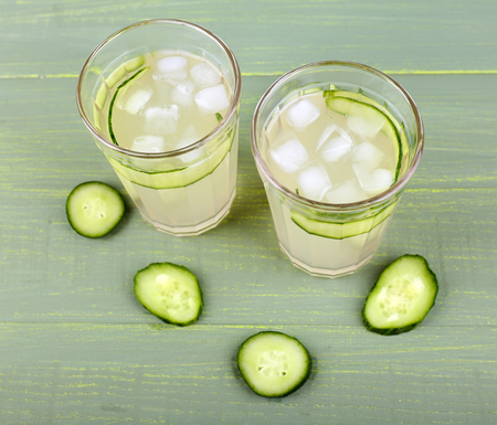 clarification: Two glasses of cucumber cocktail on wooden background