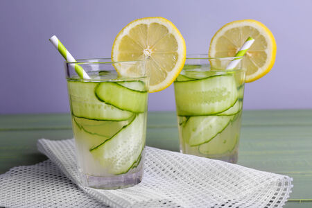 clarification: Two glasses of cucumber cocktail on napkin on wooden table on light background Stock Photo
