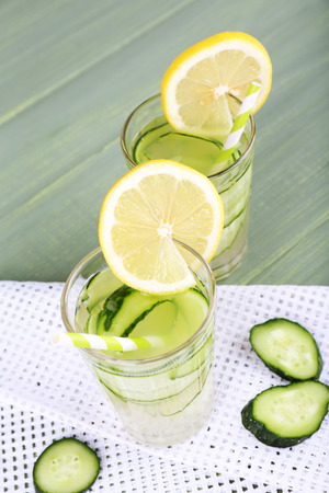 clarification: Two glasses of cucumber cocktail on napkin on wooden background