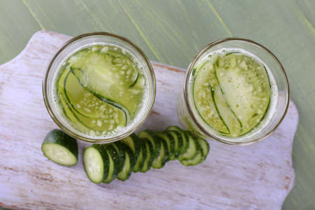 clarification: Glasses of cucumber cocktail on cutting board on wooden background Stock Photo