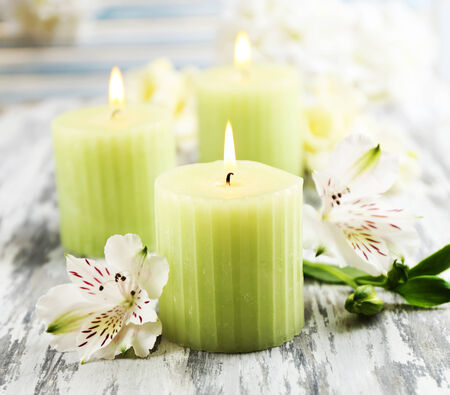 candle: Beautiful candles with flowers on wooden background Stock Photo