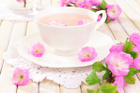 Beautiful fruit blossom with cup of tea on table on light background photo