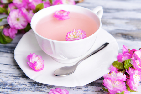 Beautiful fruit blossom with cup of tea on table close-up photo