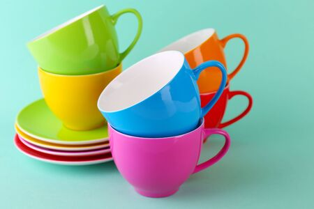 saucers: Colorful cups and saucers on color background