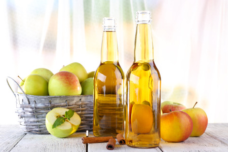 Stilleben mit Apfelwein und frische Äpfel auf Holztisch Lizenzfreie Bilder