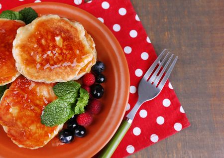 Tasty pancakes with fresh berries, honey and mint leaf on plate, on  wooden background photo