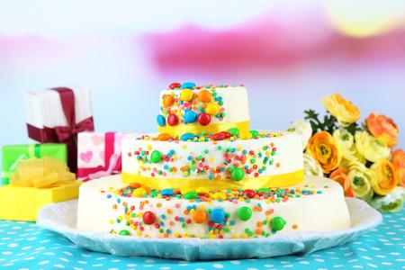 cake birthday: Beautiful tasty birthday cake and gifts on light background