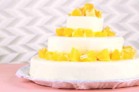 three layer: Beautiful wedding cake with oranges on  light background