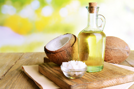 coco: El aceite de coco en la mesa sobre fondo claro