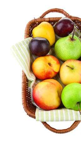 Assortment of juicy fruits in wicker basket, isolated on white photo