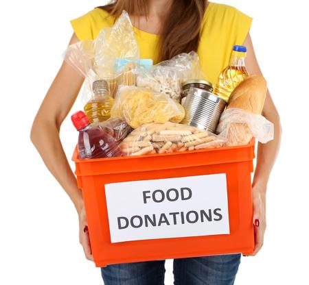 produits alimentaires: Fille bénévole boîte de dons avec les denrées alimentaires isolé sur blanc
