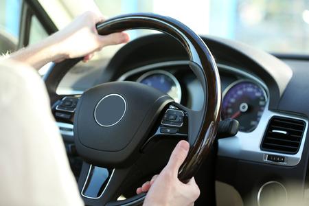 wheel: Mans hands on a steering wheel