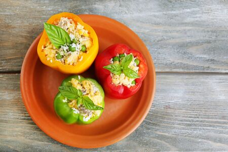 Peppers prepared for cooking stuffed paprika with meat and rice, on plate, on wooden background photo
