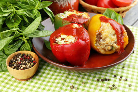 Composition with prepared stuffed peppers on plate and fresh herbs, spices and vegetables, on wooden background photo