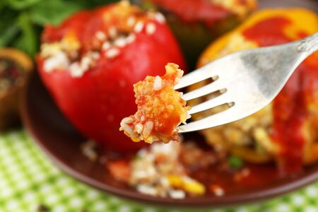 Fork with piece of stuffed pepper, close-up photo