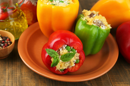 Peppers prepared for cooking with meat and rice, on plate, on wooden background photo