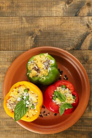 Peppers prepared for cooking stuffed paprika with meat and rice, on plate, on wooden background