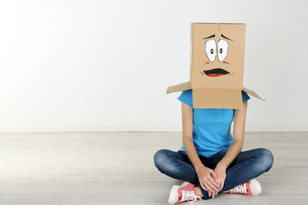 cara triste: Mujer con caja de cartón en la cabeza con la cara triste, cerca de la pared