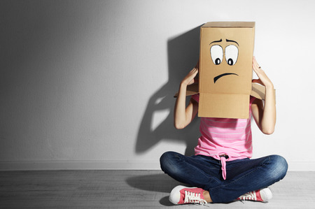Woman with cardboard box on her head with sad face, near wall Stockfoto